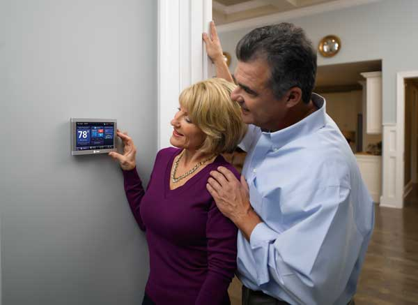 Man and woman adjusting thermostat on wall set at 78 degrees